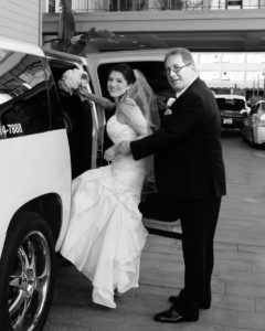 Dad helping the bride into the limo