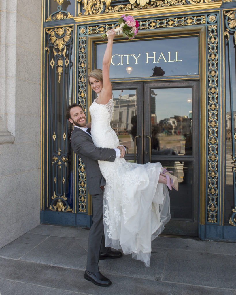 Bride Cheering in front of the city hall sign