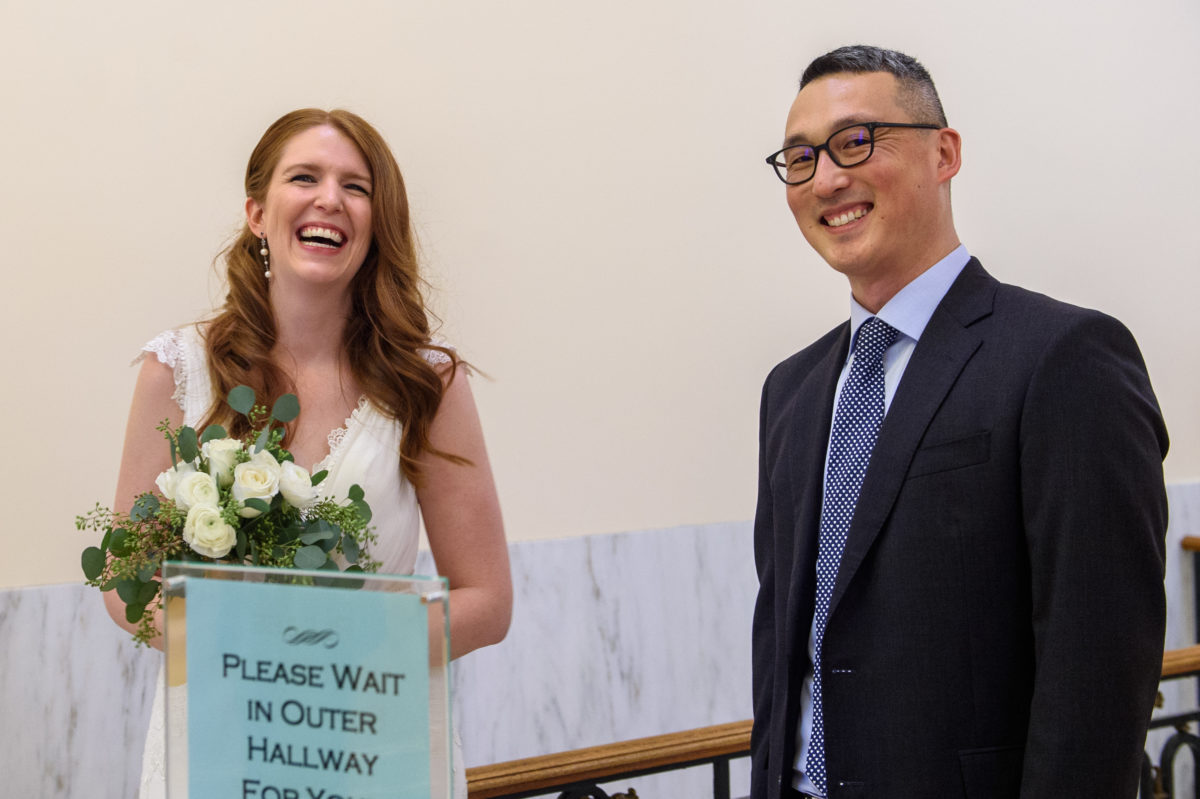 Candid shot of the couple checking in for their city hall wedding in San Francisco, CA