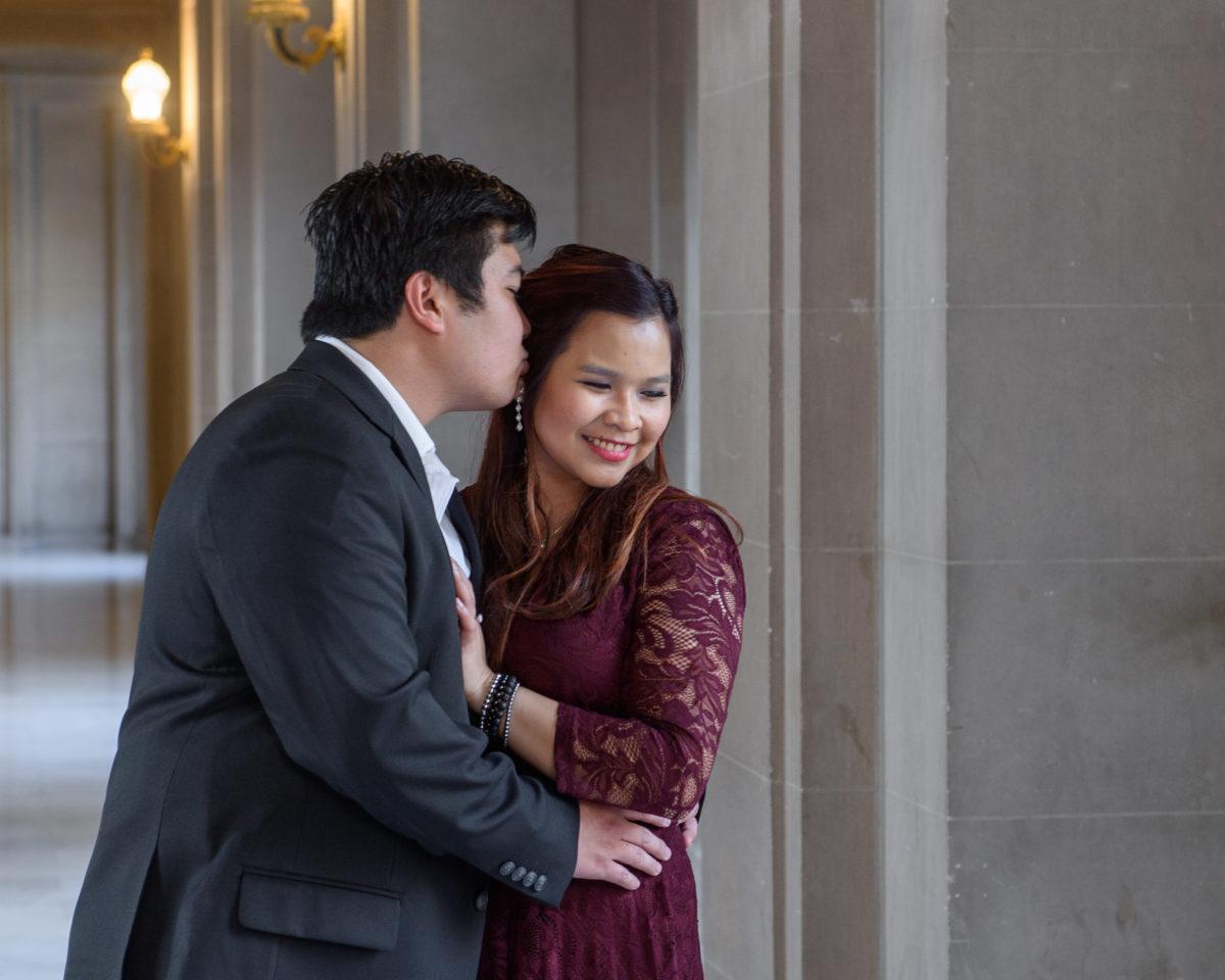 Groom kissing bride on the 3rd floor of SF City Hall