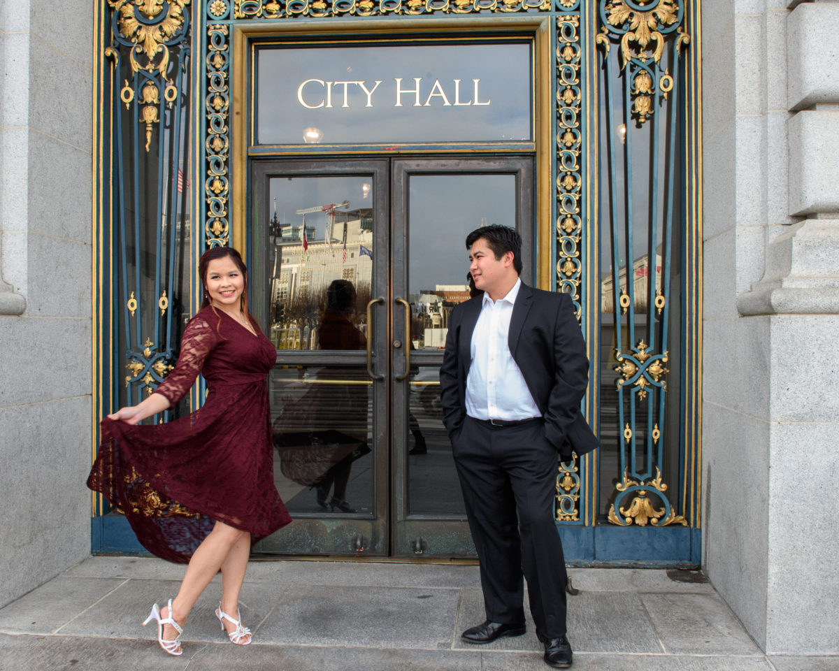 Bride and groom in front of city hall sign while twirling her dress.