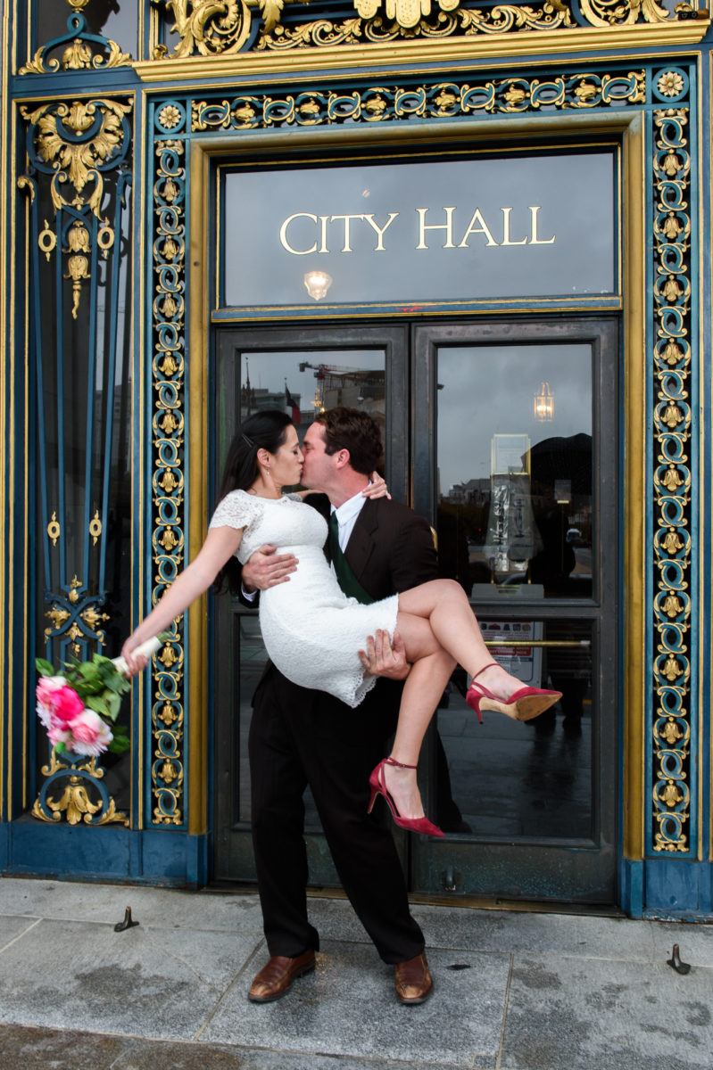 San Francisco city hall wedding picture at the front entrance - groom kissing bride