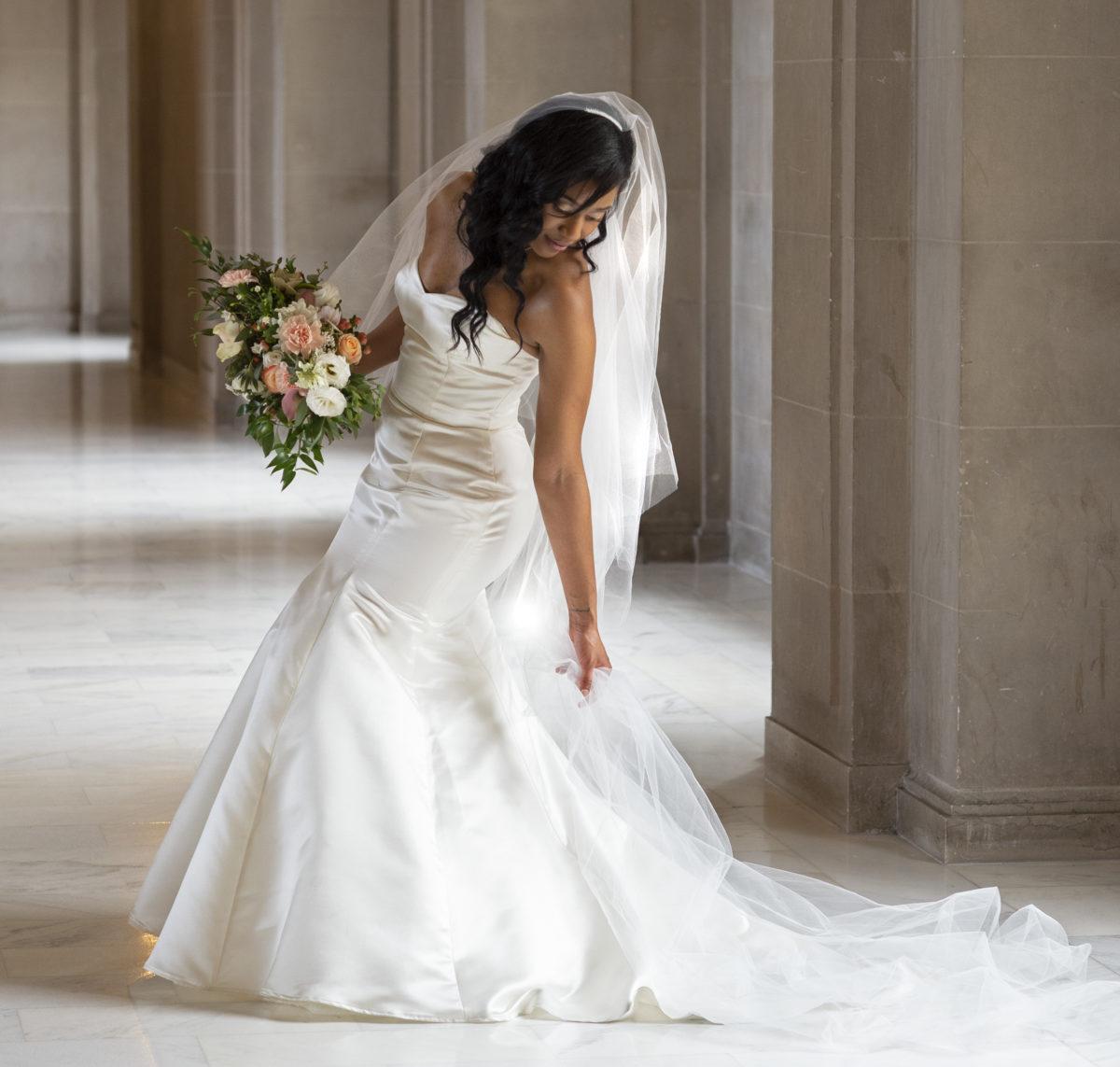 Bride adjusting dress close to the Mayors Balcony.