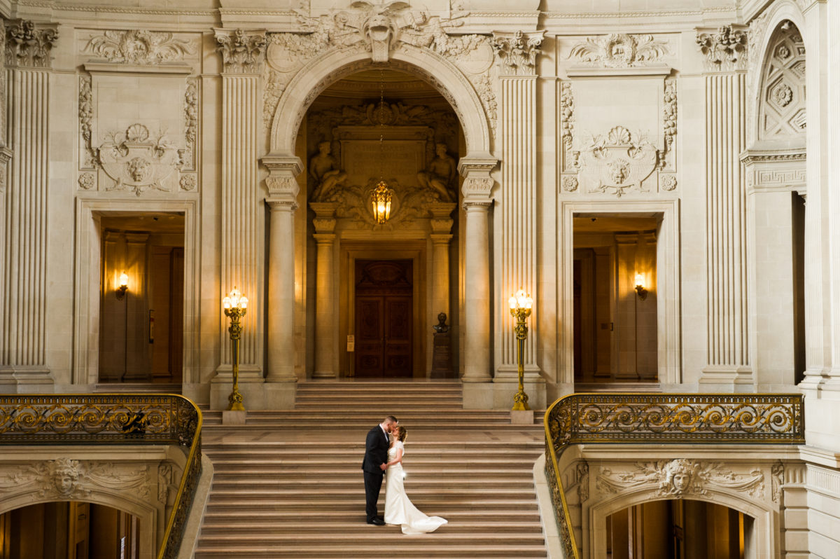 Top of the Grand Staircase SF City Hall bride and groom